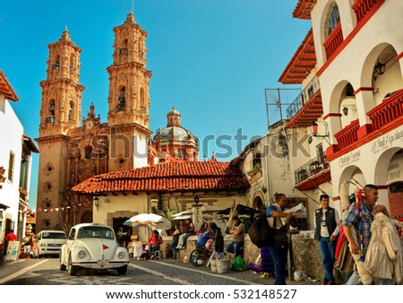 Taxco, Mexico - November 19, 2016: Mini taxi (Volkswagen Beetle) against the Cathedral of Taxco, Mexico.