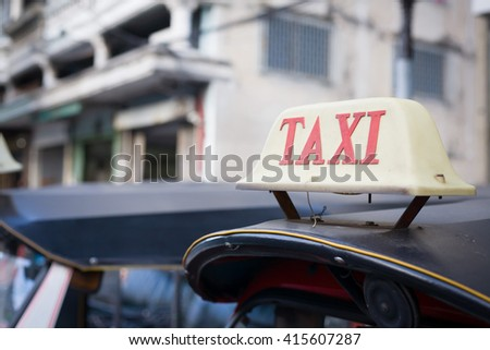 Taxi is called Tuk-Tuk scooters. Bangkok, Thailand. (selective focus on Taxi sign on roof)