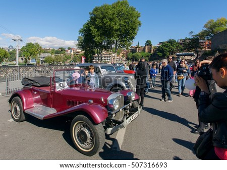 TBILISI, GEORGIA - OCT 16: Family making photo in the crowd outside during the antique car show of the Tbilisoba on October 16 2016. Tbilisoba is traditional festival in Tbilisi from 1979