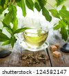 Tea on wooden boards with green leaves - stock photo