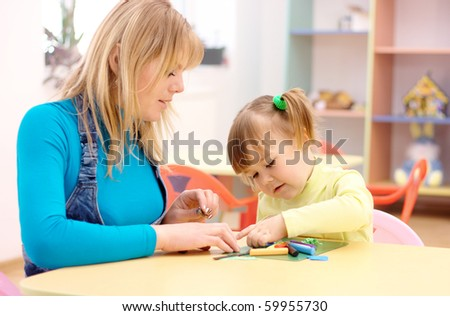 Teacher and cute little girl play with plasticine in preschool