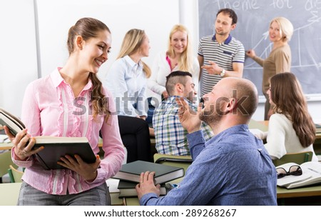 Teacher and happy adult students during break in classroom