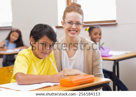 Teacher and pupil smiling at camera at the elementary school