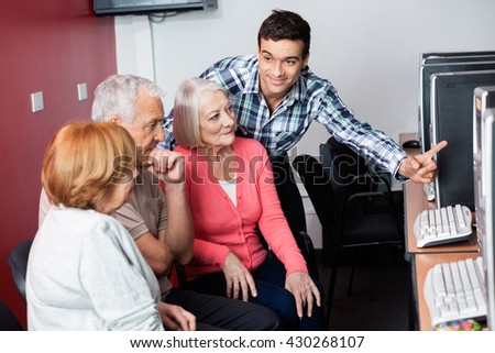 Teacher Assisting Senior Students In Using Computer At Class