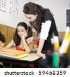 Teacher helping out a student in need - stock photo