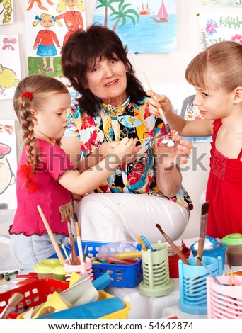 Teacher learn children painting picture  in preschool.