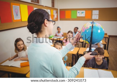 Teacher showing pupils a globe at the elementary school