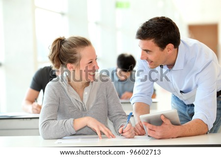 Teacher with student girl writing assignment