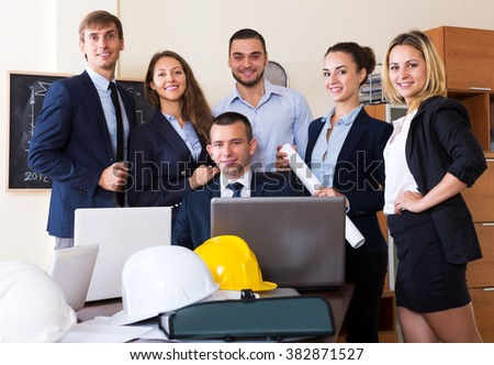 Team of architectural engineers with laptops and blueprints in office