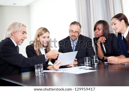 Team of businesspeople working together discussing in the office - looking at the notepad