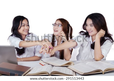 Team of female students doing homework together and pile up their hands, isolated on white