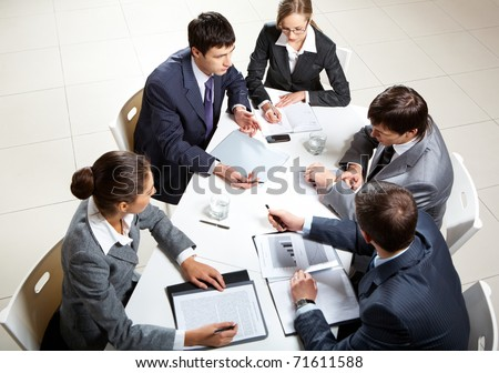 Team of five business people discussing an important question at briefing