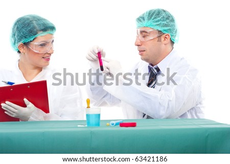 Team of two scientists people examine blood tube .Man pointing on tube and woman writing in clipboard