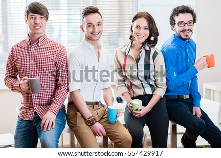 Team of young creative business people in office, one woman and three men