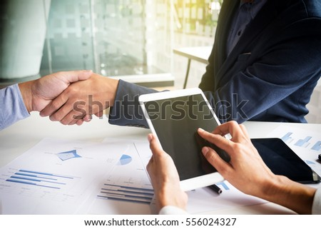Teamwork concept of office working, Young business men shaking hands with document graph background.
