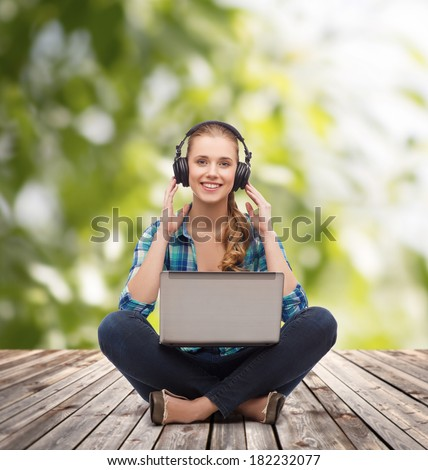 technology, internet and people concept - smiling young woman in casual clothes sitiing on floor with laptop computer and headphones