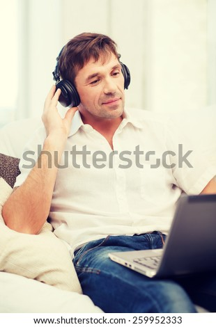 technology, leisure and lifestyle concept - happy man with headphones listening to music at home