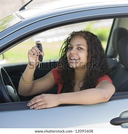 Teen driver inside car with keys smiles