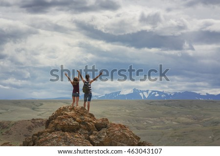 Teen girl and a guy on a mountain top