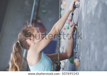 Teen girl climbing a rock wall indoor