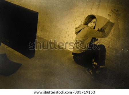 teen girl cyber abused suffering internet cyberbullying scared and desperate in fear face expression sitting on the floor in front of computer monitor in  bullying social problem edgy grunge lighting