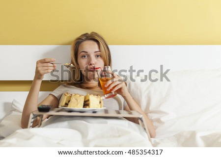 Teen girl drinking soda, eating cake in bed and watching TV