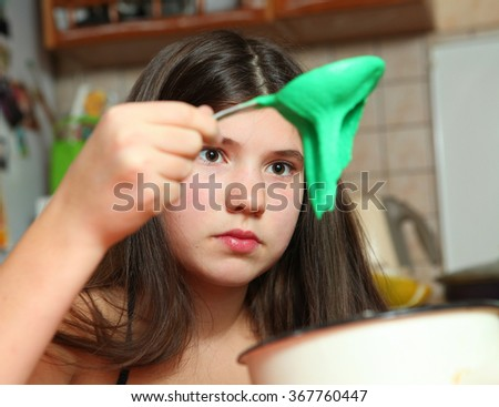 teen girl with long dark hair cooking macaroons cookies from green color dough in the kitchen