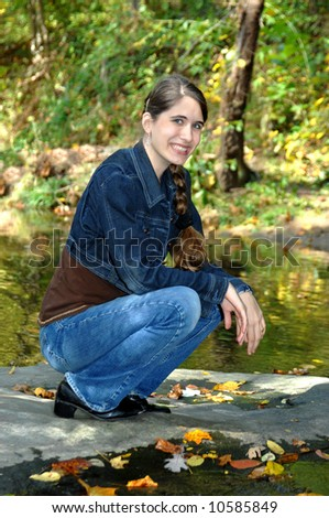 Teen relaxes besides a brook.  Fall leaves float on the water.  Denim jacket and jeans.  Smiling.
