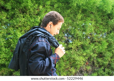 Teen with ear-phone on green bush background.