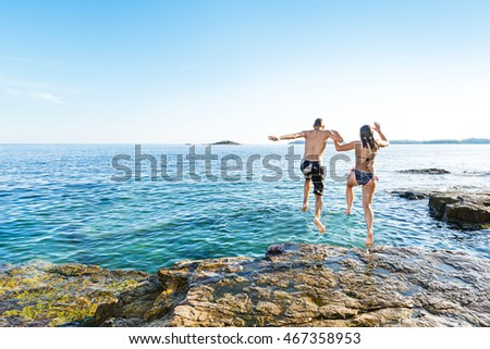 Teenage boy and a girl jumping together into the sea