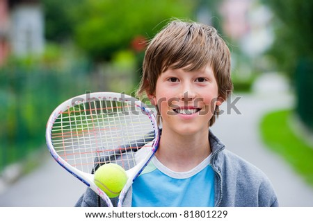 Teenage boy smiling while holding a tennis racket and ball.