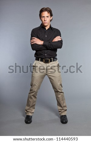 Teenage boy with brown hair and eyes. Wearing black shirt and khaki pants. Good looking. Casual wear. Expressions. Studio portrait isolated on grey background.