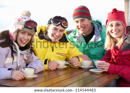 Teenage Family Enjoying Hot Drink In Cafe At Ski Resort