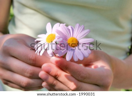 Teenage girl holding two pink daisies