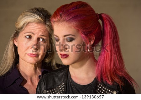 Teenage girl looking down with sympathetic woman next to her