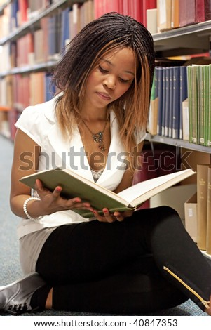 Teenage girl reading a book in the library