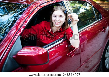 Teenage girl with her driver's license driving a new car and holding keys.