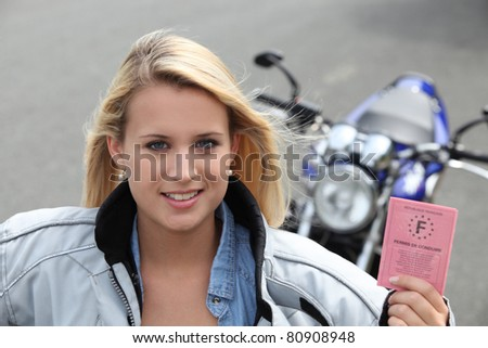 Teenage girl with motorbike and driving license