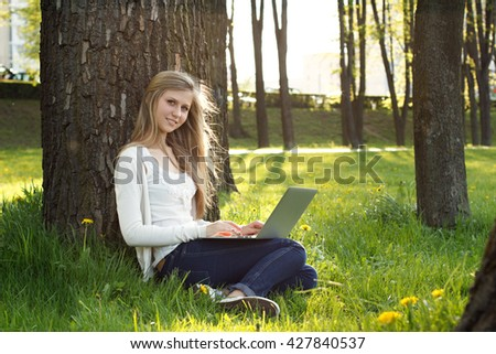 Teenage girl working with laptop in park on sunny summer day. Summer courses, college, back to school concept.