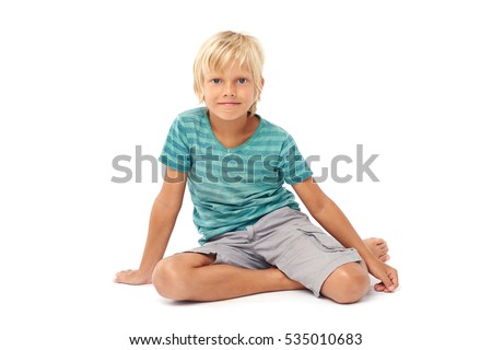 Teenage smiling blond boy sitting on the floor