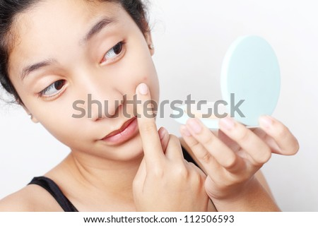 Teenager checking her face for pimple in the mirror.
