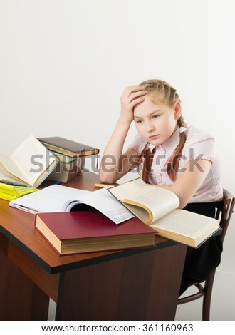 teenager girl sitting at a table in front of her large pile of books. schoolgirl reading a book and doing homework