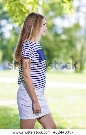 Teenager Lifestyle Concepts and Ideas.Blond Caucasian Teenager Girl Posing Outdoors in Park. Vertical Image Composition
