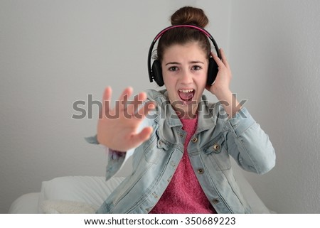 teenager listening to music with headphones in Senta given in the bed of your room