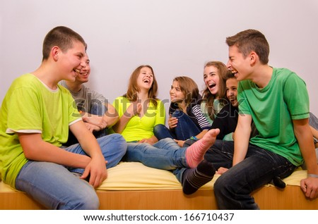 Teenagers having fun at home while sitting on bed.