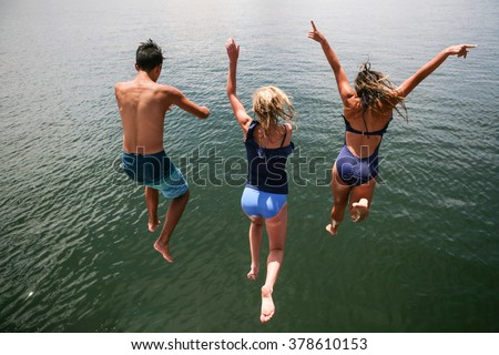 Teenagers in swimsuits leaping into lake from high up on sunny summer day