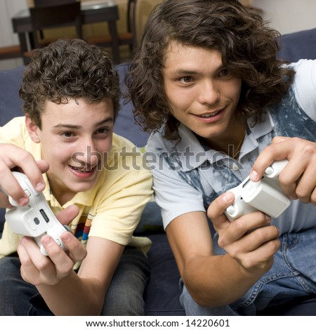 Teens play video games on a couch
