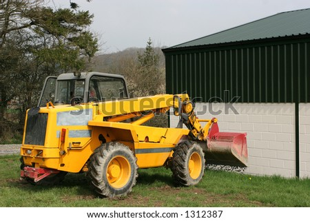 Telescopic loader tipping gravel next to a building,