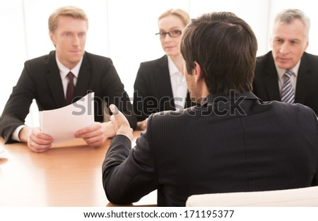 Telling about his work experience. Three people in formalwear interviewing young man sitting back to camera