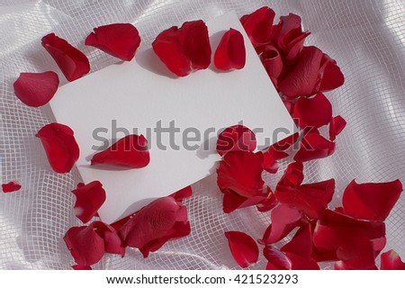 Template greeting card on the wedding day, birthdays, anniversaries and other celebrations. Rose petals with a veil on a fabric background.